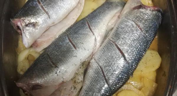 pasado este tiempo pondremos el pescado la lubina encima de la cama de patatas y cebolla