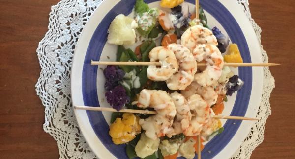 Lavar la coliflor de colores, junto con la zanahoria y judías verdes, todo troceado . Los gambones previamente los hemos detener descongelados con el agua de mar. Una vez descongelados, y para macerarlos ,  se retira el agua, ya escurridos  por  un colador , y en un bol  se le  añadiría las 2 cucharadas de aceite de  sésamo durante 6/7 minutos.  Una vez transcurridos los 5minutos, le añadimos las verduras , añadiendo 9 minutos de nuevo.  Mientras esperamos que nos avise , preparamos las brochetas , y  las  añadimos a las verduras , durante  1 minuto mas.  Todo este tiempo, de 15 minutos, habremos realizado, las peras al vino blanco , las verduras y las brochetas-