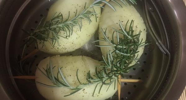 Se preparan las patatas, se pelan y se le inserta el palillo de brocheta , y con un cuchillo afilado, se va cortando la patata en forma de  espiral . Se colocan en la Softiera , aliñadas con sal y  pimienta , junto con unas ramitas de romero fresco por encima.  En la unidad de 20 cm, se le ponen vaso de agua, sin sobrepasar los agujeros  de la Softiera, se pone también unas ramitas de romero y  se introduce la Softiera con las patatas ya preparadas- Ponemos la Tapa Rapida , el Audio en Soft, durante 5´, y el Navigenio en el numero 6.